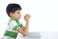 Muchacho indio que ruega con el ordenador portátil Fotos de archivo