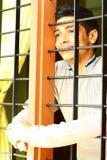 Muchacho indio soñador que mira hacia fuera a través de la ventana Fotos de archivo libres de regalías
