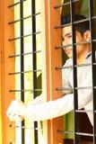 Muchacho indio solo que mira hacia fuera a través de la ventana Imagenes de archivo
