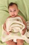 Muchacho infantil que miente en las mantas del bebé que desgastan un pañal Imagenes de archivo