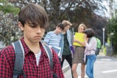 Muchacho infeliz que es cotilleado alrededor por los amigos de la escuela Foto de archivo libre de regalías