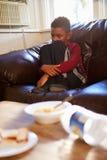 Muchacho infeliz que se sienta en Sofa At Home Imagen de archivo libre de regalías