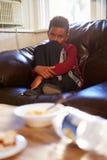 Muchacho infeliz que se sienta en Sofa At Home Imagenes de archivo