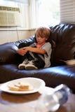 Muchacho infeliz que se sienta en Sofa At Home Imagen de archivo