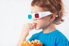 Muchacho irónico joven en vidrios estéreos que come las palomitas Foto de archivo