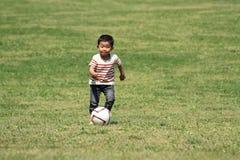 Muchacho japonés que golpea un balón de fútbol con el pie Fotos de archivo