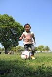 Muchacho japonés que golpea un balón de fútbol con el pie Imagenes de archivo