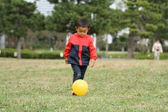 Muchacho japonés que golpea una bola con el pie amarilla en la hierba fotografía de archivo