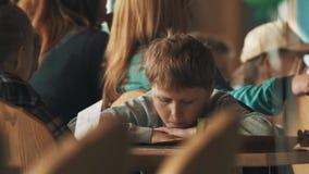 Muchacho joven aburrido en el evento apretado Ponga la cabeza en los brazos, leyendo el folleto almacen de metraje de vídeo