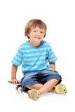 Muchacho joven adorable que se sienta en un patín Fotografía de archivo libre de regalías