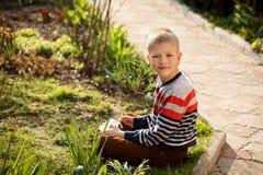 Muchacho joven al aire libre en la hierba en el patio trasero usando su COM de la tableta Fotografía de archivo