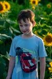 Muchacho joven alegre de la belleza con el girasol que disfruta de la naturaleza y que ríe en campo del girasol del verano Sunfla Foto de archivo