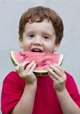 Muchacho joven alrededor para comer un pedazo de sandía Fotos de archivo libres de regalías