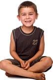 Muchacho joven asentado con la risa sucia de los pies Imagen de archivo