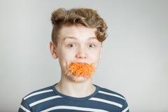 Muchacho joven asombroso con un bocado de la zanahoria Fotografía de archivo libre de regalías