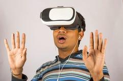 Muchacho joven asustado con las gafas de la realidad virtual y goce en vídeo asustadizo de 3D VR Imagen de archivo libre de regalías