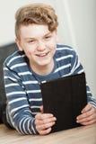 Muchacho joven atractivo feliz con una tableta-PC Fotografía de archivo