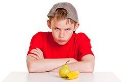 Muchacho joven beligerante con la fruta Fotografía de archivo