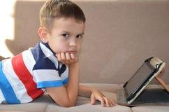 Muchacho joven cansado con los vidrios que sientan y que llevan a cabo su cabeza en la tableta delante del ordenador, la tableta  Imágenes de archivo libres de regalías