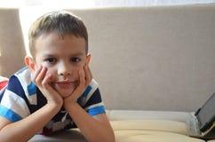 Muchacho joven cansado con los vidrios que sientan y que llevan a cabo su cabeza en la tableta delante del ordenador, la tableta  Imagen de archivo libre de regalías