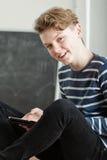 Muchacho joven carismático que usa una tableta Imagenes de archivo