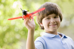 Muchacho joven con el aeroplano del juguete al aire libre que sonríe Foto de archivo libre de regalías