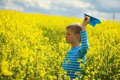 Muchacho joven con el avión de papel contra el cielo azul y el campo amarillo Flo Foto de archivo