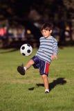 Muchacho joven con el balón de fútbol en parque Imágenes de archivo libres de regalías