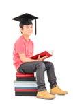 Muchacho joven con el birrete asentado en una pila de libros Fotografía de archivo