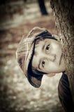 Muchacho joven con el casquillo del vendedor de periódicos que juega al detective Fotos de archivo libres de regalías