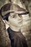 Muchacho joven con el casquillo del vendedor de periódicos que juega al detective Imágenes de archivo libres de regalías