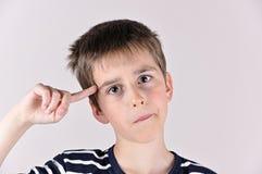 Muchacho joven con el dedo índice en su cabeza Foto de archivo libre de regalías