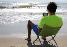 Muchacho joven con el ebook en la costa en verano Foto de archivo libre de regalías
