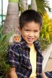 Muchacho joven con el hámster del animal doméstico en su hombro Foto de archivo