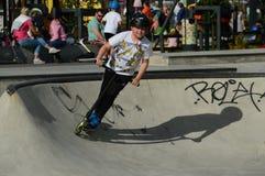 Muchacho joven con el kickbike en la rampa en un Skatepark Espoo, Finlandia Foto de archivo