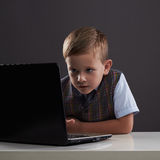 Muchacho joven con el ordenador niño divertido que mira en cuaderno Imagen de archivo