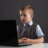 Muchacho joven con el ordenador niño divertido que mira en cuaderno Imágenes de archivo libres de regalías