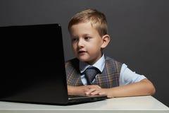 Muchacho joven con el ordenador niño divertido que mira en cuaderno Foto de archivo libre de regalías