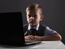 Muchacho joven con el ordenador niño divertido que mira en cuaderno Fotos de archivo libres de regalías