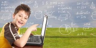 Muchacho joven con el ordenador portátil. Fotografía de archivo