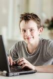 Muchacho joven con el ordenador portátil que sonríe en la cámara Imagen de archivo