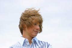 Muchacho joven con el pelo azotado por el viento foto de archivo