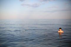 Muchacho joven con el pelo marrón mientras que se baña en el mar Fotografía de archivo libre de regalías