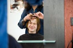 Muchacho joven con el pelo rojo en el peluquero Imagen de archivo libre de regalías