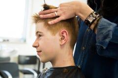 Muchacho joven con el pelo rojo que consigue un corte de pelo Imagen de archivo