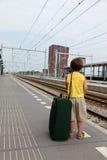 Muchacho joven con el tren que espera del equipaje para foto de archivo