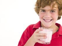 Muchacho joven con el vidrio de sonrisa de la leche Fotos de archivo