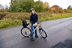 Muchacho joven con la bici en viaje por la lluvia Imagenes de archivo
