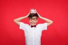 Muchacho joven con la caja de regalo en la cabeza Imagenes de archivo