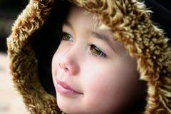 Muchacho joven con la capa encapuchada mullida del invierno Imágenes de archivo libres de regalías